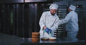 Ένας chubby ελκυστικός νέος τύπος αρχιμαγείρων διακόσμησε το εσωτερικό του κέικ με την άσπρη χνουδωτή κρέμα που προέρχεται από έν απόθεμα βίντεο