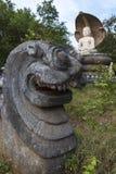 Ένα άγαλμα δράκων κάθεται μπροστά από το άγαλμα του Βούδα στο ναό Pidurangala σε Sigiriya στη Σρι Λάνκα Στοκ εικόνες με δικαίωμα ελεύθερης χρήσης