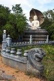 Ένα άγαλμα δράκων κάθεται μπροστά από το άγαλμα του Βούδα στο ναό Pidurangala σε Sigiriya στη Σρι Λάνκα Στοκ Εικόνες
