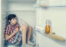 Ένα άγρυπνο αγόρι σε ένα πουκάμισο και τα σορτς που τρώνε έναν croissant και πίνουν το γάλα μέσα σε ένα ψυγείο με τα τρόφιμα και  Στοκ Εικόνες
