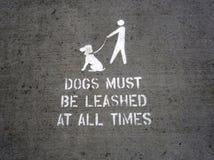 Ένα άσπρο διάτρητο σε ένα τσιμεντένιο πάτωμα που δηλώνει τα σκυλιά πρέπει να δέσει στοκ εικόνες