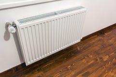Ένα άσπρο θερμαντικό σώμα θέρμανσης στον εσωτερικό τοίχο στοκ εικόνες