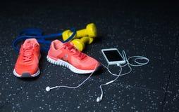 Ένα άσπρο κινητό τηλέφωνο με τα ακουστικά, τα ρόδινα πάνινα παπούτσια, δύο κίτρινους αλτήρες και αποσυμπιεστή σε ένα θολωμένο υπό Στοκ φωτογραφίες με δικαίωμα ελεύθερης χρήσης