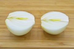 Ένα άσπρο κρεμμύδι ξεφλουδίζει και που χωρίζει ξεφλουδισμένος στοκ φωτογραφία