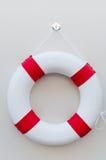Ένα άσπρο κόκκινο Lifebuoy με έναν πίνακα στον άσπρο τοίχο Στοκ Εικόνες