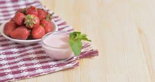 Ένα άσπρο πιάτο με τις ώριμες φράουλες είναι σε μια πετσέτα Στοκ φωτογραφία με δικαίωμα ελεύθερης χρήσης