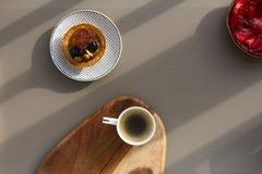 Ένα άσπρο φλυτζάνι του espresso με το γάλα σε ένα ξύλινο υπόβαθρο και τα κέικ με τα καρύδια και των φραουλών σε ένα γκρίζο υπόβαθ Στοκ εικόνες με δικαίωμα ελεύθερης χρήσης