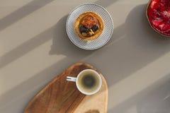Ένα άσπρο φλυτζάνι του espresso με το γάλα σε ένα ξύλινο υπόβαθρο και τα κέικ με τα καρύδια και των φραουλών σε ένα γκρίζο υπόβαθ Στοκ Εικόνες