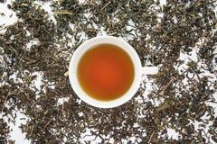 Ένα άσπρο φλυτζάνι του τσαγιού στο ξηρό φύλλο τσαγιού στοκ φωτογραφία με δικαίωμα ελεύθερης χρήσης