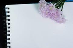 Ένα άσπρο sketchbook και ένα ρόδινο λουλούδι στοκ εικόνες