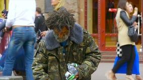 Ένα άστεγο ηλικιωμένο άτομο κοιτάζει μέσω ενός δοχείου απορριμμάτων σε μια πολυάσχολη οδό πόλεων, ο ηληκιωμένος επαιτών που ψάχνε απόθεμα βίντεο