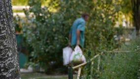 Ένα άστεγο ηλικιωμένο άτομο φέρνει τις συσκευασίες, ένας επαίτης συλλέγει τα κενά μπουκάλια σε ένα πακέτο απόθεμα βίντεο