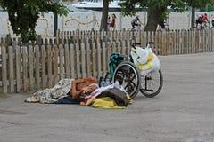 Ένα άστεγο με ειδικές ανάγκες άτομο με έναν ύπνο αναπηρικών καρεκλών στην άσφαλτο στη Βαρκελώνη στοκ εικόνες