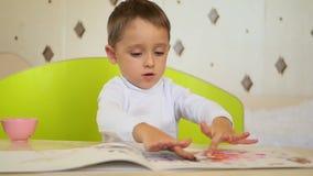 Ένα άτακτο αγόρι παίρνει το χρώμα και χτυπά τους φοίνικές του σε χαρτί Ανάπτυξη, εκπαίδευση, ψυχολογία, συγκινήσεις ενός παιδιού απόθεμα βίντεο