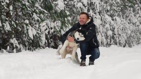 Ένα άτομο αγκαλιάζει το Σιβηριανό του γεροδεμένο στο δάσος στα δέντρα υποβάθρου στο χιόνι Υπερηφάνεια και ευτυχία στα μάτια περίπ απόθεμα βίντεο