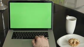 Ένα άτομο δακτυλογραφεί σε ένα lap-top στο γραφείο του φιλμ μικρού μήκους