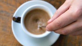 Ένα άτομο ανακατώνει τον καφέ σε έναν καφέ με ένα κουτάλι Εστίαση σε διαθεσιμότητα φιλμ μικρού μήκους