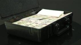 Ένα άτομο ανοίγει μια μαύρη βαλίτσα μετάλλων με τα χρήματα φιλμ μικρού μήκους