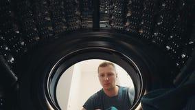 Ένα άτομο ανοίγει την πόρτα και φορτώνει το πλυντήριο στο πλυντήριο απόθεμα βίντεο