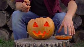 Ένα άτομο βάζει ένα καίγοντας κερί στο φανάρι του Jack ` s Στο κατώφλι στο κολόβωμα απόθεμα βίντεο