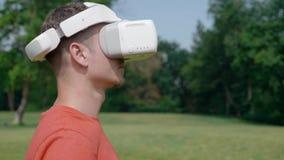 Ένα άτομο βάζει μια κάσκα VR στο κεφάλι του σε ένα πάρκο φιλμ μικρού μήκους