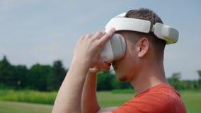 Ένα άτομο βάζει μια κάσκα VR στο κεφάλι του σε ένα πάρκο απόθεμα βίντεο
