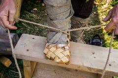Ένα άτομο βάζει σε ένα παπούτσι ίνας ραφίας Στοκ Φωτογραφία