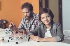 Ένα άτομο βοηθά ένα αγόρι με μια συνέλευση ρομπότ Το αγόρι εξετάζει τη κάμερα ενώ το άτομο συγκεντρώνει το ρομπότ Στοκ Φωτογραφίες