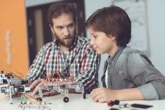 Ένα άτομο βοηθά ένα αγόρι με μια συνέλευση ρομπότ Το αγόρι κοιτάζει προσεκτικά δεδομένου ότι ένα άτομο συλλέγει ένα ρομπότ Στοκ φωτογραφία με δικαίωμα ελεύθερης χρήσης