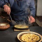 Ένα άτομο γυρίζει μια καυτή τηγανίτα σε ένα τηγάνι με spatula στοκ φωτογραφία με δικαίωμα ελεύθερης χρήσης