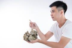 Ένα άτομο δίνει την μπουλέττα zongzi ή ρυζιού σε άλλοι ως παρόν ή αναμνηστικό στο φεστιβάλ βαρκών δράκων, ασιατικά παραδοσιακά τρ στοκ εικόνα με δικαίωμα ελεύθερης χρήσης