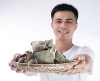 Ένα άτομο δίνει την μπουλέττα zongzi ή ρυζιού σε άλλοι ως παρόν ή αναμνηστικό στο φεστιβάλ βαρκών δράκων, ασιατικά παραδοσιακά τρ στοκ φωτογραφία με δικαίωμα ελεύθερης χρήσης