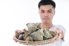 Ένα άτομο δίνει την μπουλέττα zongzi ή ρυζιού σε άλλοι ως παρόν ή αναμνηστικό στο φεστιβάλ βαρκών δράκων, ασιατικά παραδοσιακά τρ στοκ εικόνες με δικαίωμα ελεύθερης χρήσης