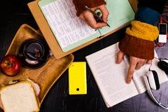 Ένα άτομο διαβάζει, μεταφράζει το κείμενο Σάντουιτς, ακουστικά, μολύβια, σημειωματάρια Ακόμα ζωή, μαύρο υπόβαθρο Στοκ φωτογραφία με δικαίωμα ελεύθερης χρήσης