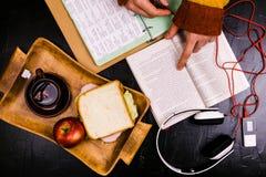Ένα άτομο διαβάζει, μεταφράζει το κείμενο Σάντουιτς, ακουστικά, μολύβια, σημειωματάρια Ακόμα ζωή, μαύρο υπόβαθρο Στοκ Εικόνες