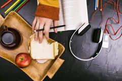 Ένα άτομο διαβάζει, μεταφράζει το κείμενο Σάντουιτς, ακουστικά, μολύβια, σημειωματάρια Ακόμα ζωή, μαύρο υπόβαθρο Στοκ εικόνα με δικαίωμα ελεύθερης χρήσης