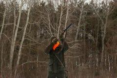 Ένα άτομο είναι κυνηγός σε ένα χειμερινό δασικό κυνήγι για το παιχνίδι Ο κυνηγός πυροβολεί ένα πουλί σε ένα δασικό ξέφωτο Φασιανό στοκ εικόνα με δικαίωμα ελεύθερης χρήσης