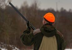 Ένα άτομο είναι κυνηγός σε ένα χειμερινό δασικό κυνήγι για το παιχνίδι Ο κυνηγός πυροβολεί ένα πουλί σε ένα δασικό ξέφωτο Φασιανό στοκ εικόνες
