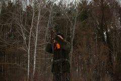 Ένα άτομο είναι κυνηγός σε ένα χειμερινό δασικό κυνήγι για το παιχνίδι Ο κυνηγός πυροβολεί ένα πουλί σε ένα δασικό ξέφωτο Φασιανό στοκ φωτογραφίες