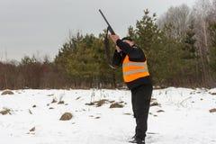 Ένα άτομο είναι κυνηγός σε ένα χειμερινό δασικό κυνήγι για το παιχνίδι Ο κυνηγός πυροβολεί ένα πουλί σε ένα δασικό ξέφωτο Φασιανό στοκ φωτογραφίες με δικαίωμα ελεύθερης χρήσης