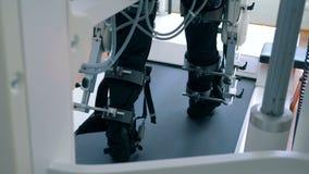 Ένα άτομο εκπαιδεύει τα πόδια του σε μια κλινική, πίσω άποψη φιλμ μικρού μήκους