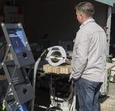 Ένα άτομο εξετάζει ένα κυκλικό πριόνι Στοκ εικόνα με δικαίωμα ελεύθερης χρήσης