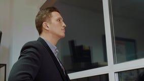 Ένα άτομο εξετάζει την πόλη βραδιού μέσω του παραθύρου μιας άποψης κινηματογραφήσεων σε πρώτο πλάνο γραφείων ουρανοξυστών απόθεμα βίντεο