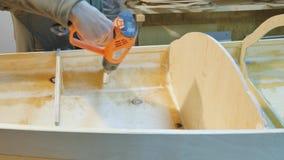 Ένα άτομο επεξεργάζεται τις ραφές της βάρκας, θερμαίνει με ένα hairdryer Αυτό γίνεται για τη συμπίεση Κατασκευή ενός σκάφους με τ απόθεμα βίντεο