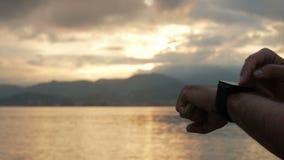 Ένα άτομο ελέγχει τα μηνύματα στο έξυπνο ρολόι κατά τη διάρκεια της ανατολής στην παραλία του ωκεανού Θαυμάσια χρώματα του ουρανο απόθεμα βίντεο