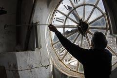 Ένα άτομο θέτει ένα ρολόι στην εκκλησία Στοκ Εικόνα