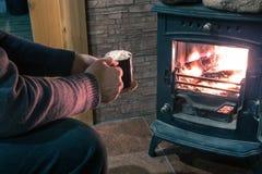 Ένα άτομο θερμαίνει και χαλαρώνει κοντά σε μια καίγοντας εστία με ένα φλιτζάνι του καφέ στα χέρια του Στοκ Εικόνα