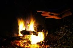 Ένα άτομο θερμαίνει τα χέρια του στην πυρκαγιά Στοκ Εικόνα