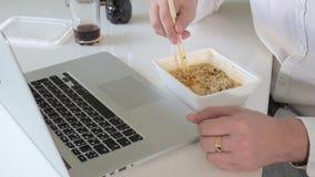 Ένα άτομο κάθεται σε έναν πίνακα που τρώει τα κινεζικά νουντλς και που λειτουργεί σε ένα lap-top απόθεμα βίντεο