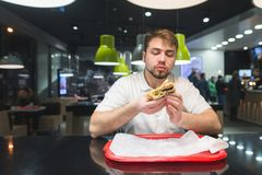 Ένα άτομο κάθεται σε ένα εστιατόριο και τρώει το γρήγορο φαγητό Το άτομο τρώει ορεκτικό burger Έννοια γρήγορου φαγητού Στοκ φωτογραφίες με δικαίωμα ελεύθερης χρήσης